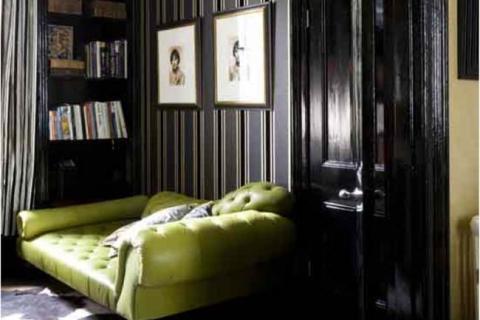 зеленый диван на фоне полосатой стены