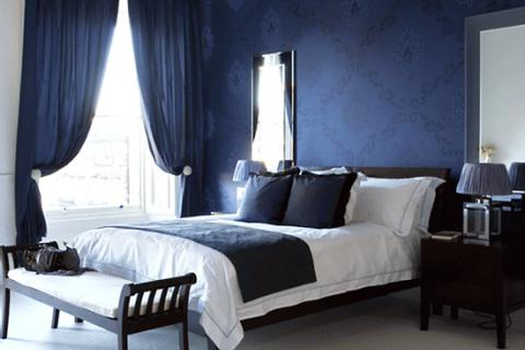 классическая спальня с темно-синими обоями и шторами