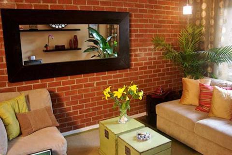 зеркало с широкой рамой на фоне кирпичной стены