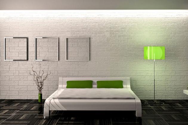 белая простая кровать на фоне белой кирпичной стены